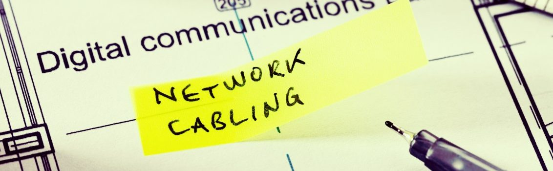 """A label on plans for a digital communications lab in an office building reads """"Network Cabling"""" on an adhesive note. Possibly instructions from the architect or electrician. A pen and a ruler lie nearby."""